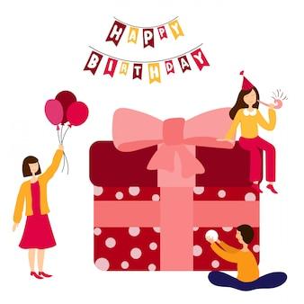 Persone insieme che decorano il regalo di compleanno gigante