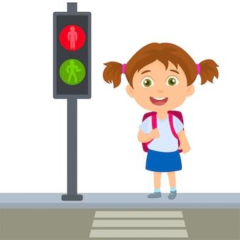 Piccola scuola ragazza che attraversa le regole permanenti pedonali