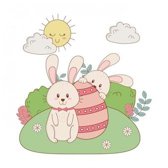 Piccoli conigli con uova dipinte nel giardino