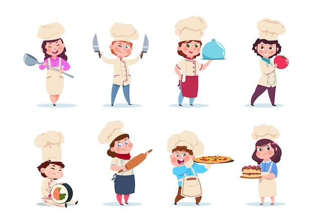 Piccoli lavoratori sorridenti della cucina della ragazza e del ragazzo con i piatti e l'insieme di strumenti di cottura