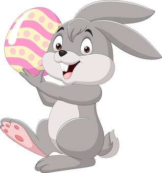 Piccolo coniglietto del fumetto che tiene l'uovo di pasqua