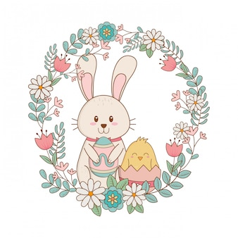 Piccolo coniglio e pulcino con uovo dipinto in corona floreale