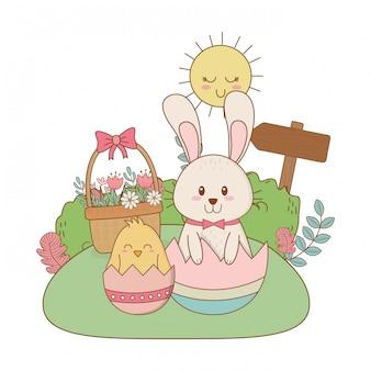 Piccolo coniglio e pulcino con uovo dipinto in giardino