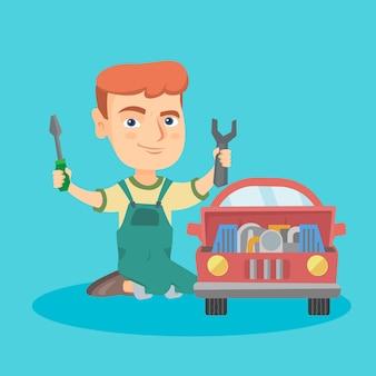 Piccolo ragazzo caucasico che ripara un'automobile del giocattolo.