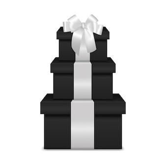 Pila di tre scatole regalo nero realistico con nastro bianco e fiocco