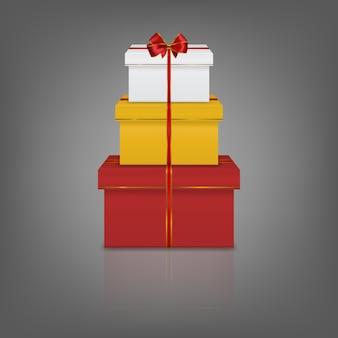 Pila di tre scatole regalo realistico con nastro rosso e fiocco