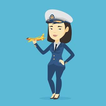 Pilota di linea aerea allegro con l'aeroplano di modello.