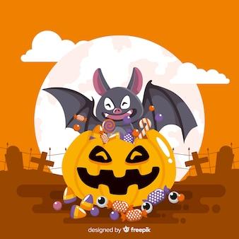 Pipistrello felice in un sacchetto di zucca pieno di caramelle