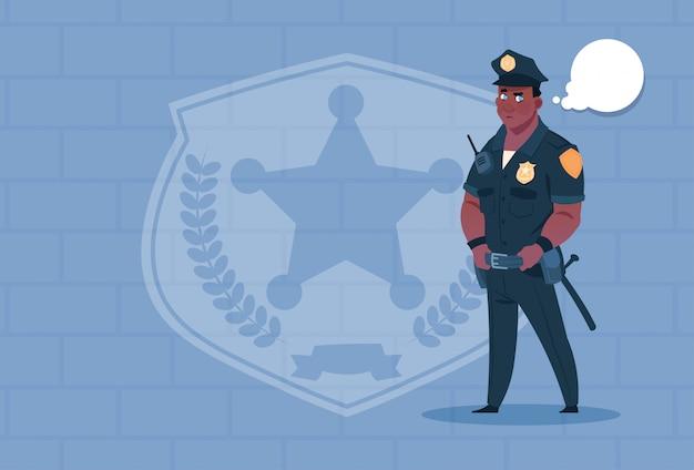Poliziotto afroamericano con la bolla di chiacchierata che indossa la guardia di uniforme uniforme sopra il fondo del mattone