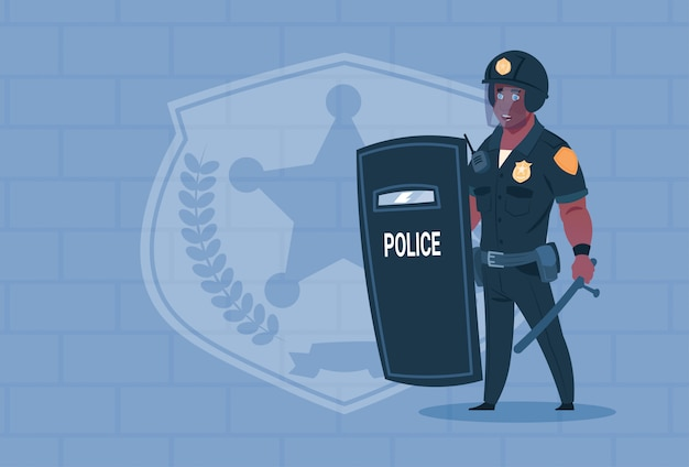 Poliziotto afroamericano tenere scudo indossando casco uniforme guardia di guardia su sfondo di mattoni