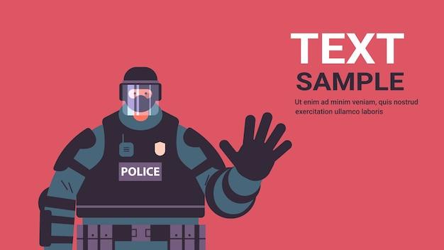 Poliziotto in completo equipaggiamento tattico poliziotto antisommossa agitando la mano manifestanti e dimostrazioni controllo concetto copia spazio