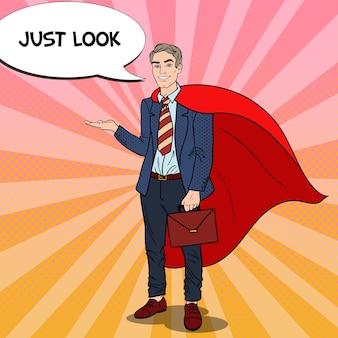 Pop art happy super uomo d'affari in capo rosso che punta sullo spazio della copia