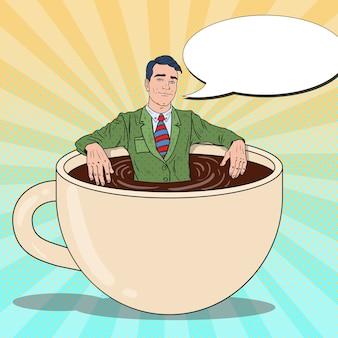 Pop art sorridente uomo d'affari rilassante nella tazza di caffè. pausa di lavoro.
