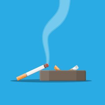 Posacenere in ceramica bianca pieno di sigarette fumanti.