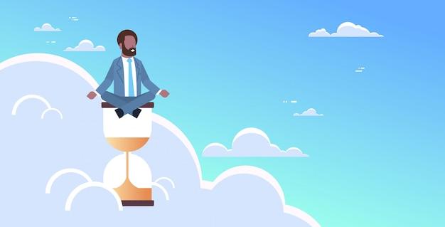 Posizione di loto di seduta dell'uomo d'affari sulla scadenza della gestione di tempo dell'orologio della sabbia concetto uomo d'affari che medita posa di yoga nel carattere maschio orizzontale del cielo integrale