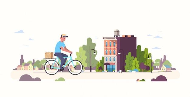 Postino in uniforme equitazione bicicletta portando cartone pacco corriere in bicicletta all'aperto espresso servizio di consegna concetto moderno paesaggio urbano