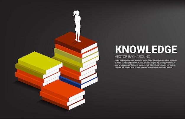 Potere della conoscenza. siluetta della donna di affari che sta sulla pila di libri.