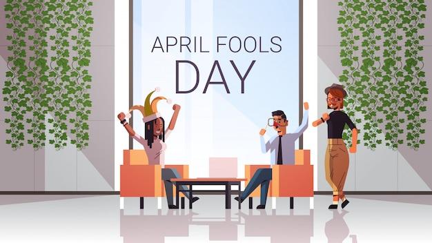 Primo aprile sciocco giorno uomini d'affari gara gara indossando buffo cappello giullare occhiali baffi festa celebrazione concetto moderno ufficio interno orizzontale integrale