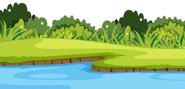 Priorità bassa del paesaggio con il fiume e l'erba verde