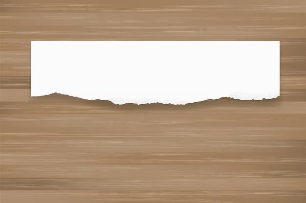Priorità bassa di carta strappata su struttura di legno marrone.