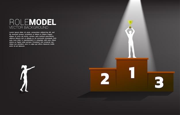 Profili il dito del punto della donna di affari all'uomo d'affari con il trofeo del campione sul podio del primo posto.