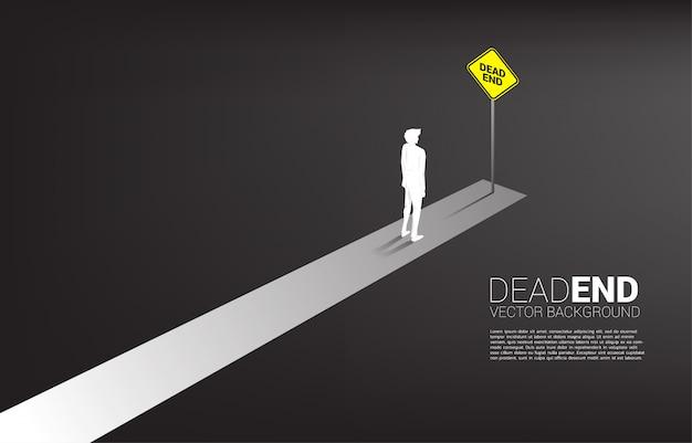 Profili l'uomo d'affari che sta all'estremità della strada con la segnaletica del vicolo cieco. decisione sbagliata negli affari o nel percorso di fine carriera.