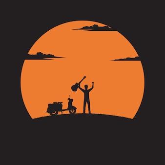 Profili la chitarra della tenuta del giovane sul fondo del tramonto
