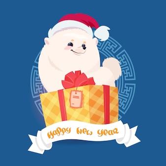 Progettazione della cartolina d'auguri del buon anno 2018 con il cane di pomerian in cappello di santa che si siede sulla grande scatola attuale