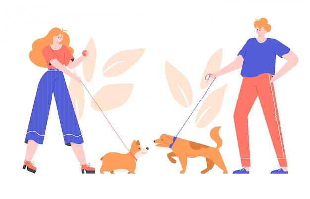 Proprietari di cani per una passeggiata. carino corgi gallese e grande cane si incontrano e giocano insieme. conoscenza di animali domestici.