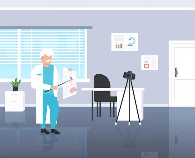 Psicologo dottore blogger spiegando il cervello umano registrando video con telecamera su treppiede medicina psicologia blogging concetto moderno clinica interno a figura intera