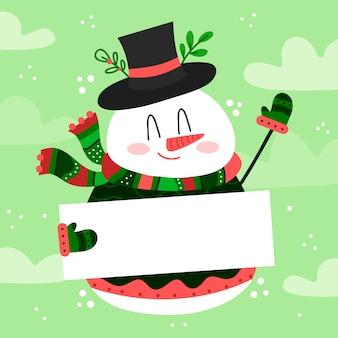 Pupazzo di neve disegnato a mano del carattere di natale che tiene insegna in bianco