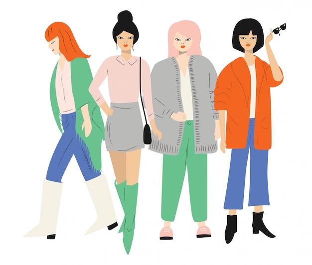 Quattro giovani donne in abiti autunnali in piedi e camminando. isolato su bianco piatto