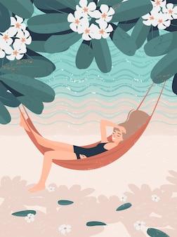 Ragazza bionda che riposa su un'amaca sul mare sotto un albero di fioritura del frangipane