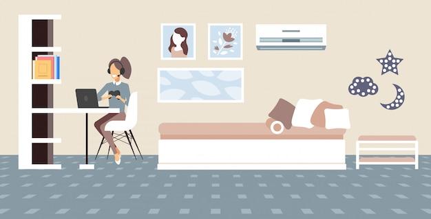 Ragazza blogger commentando il processo di gioco video recensione blogging live streaming concetto gamer in cuffia usando il gamepad giocando su laptop soggiorno interno lunghezza orizzontale