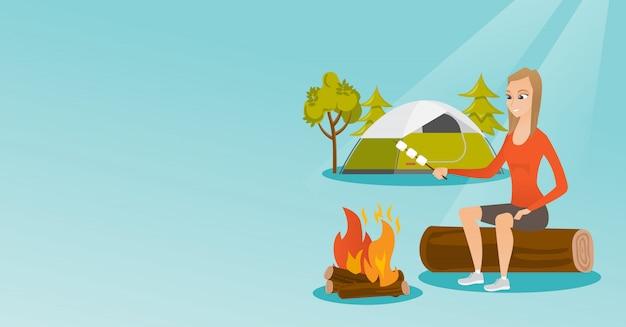 Ragazza caucasica che arrostisce marshmallow sopra fuoco di accampamento.