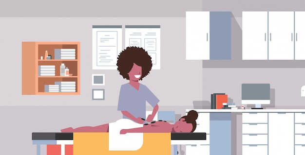 Ragazza che ha massaggiatrice di pietra calda di massaggio che massaggia menzogne di rilassamento della donna paziente del corpo sull'orizzontale interno di concetto di trattamenti interni del gabinetto medico della tavola