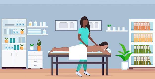 Ragazza che ha massaggiatrice posteriore di massaggio in uniforme che massaggia menzogne di rilassamento della donna paziente del corpo sull'orizzontale integrale interno moderno dell'ufficio moderno di concetto di trattamenti del letto