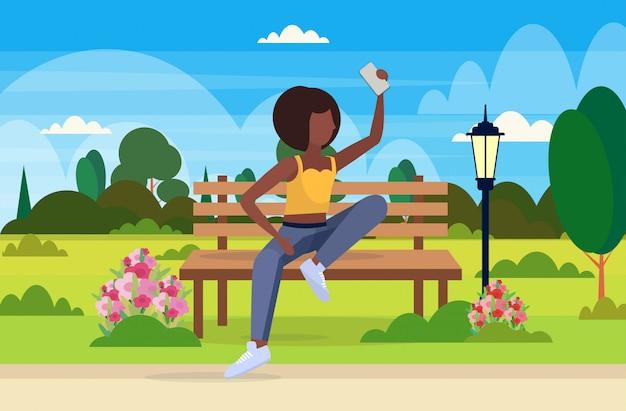 Ragazza che prende la foto del selfie sulla donna della macchina fotografica dello smartphone che si siede orizzontale orizzontale integrale femminile del personaggio dei cartoni animati del fondo del paesaggio del parco del parco di legno