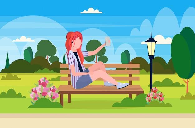 Ragazza che prende la foto del selfie sulla donna della testarossa dello smartphone che si siede orizzontale orizzontale integrale del personaggio dei cartoni animati del parco all'aperto del paesaggio del banco di legno