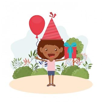 Ragazza con cappello da festa e confezione regalo in festa di compleanno