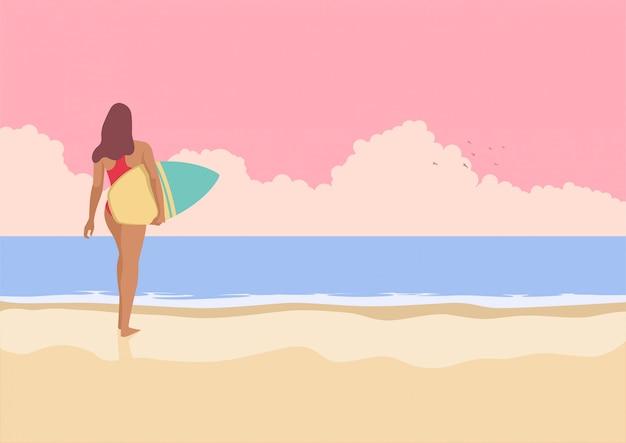 Ragazza del surfista che cammina sulla spiaggia