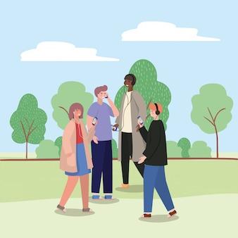 Ragazza e ragazzi con gli smartphone al parco