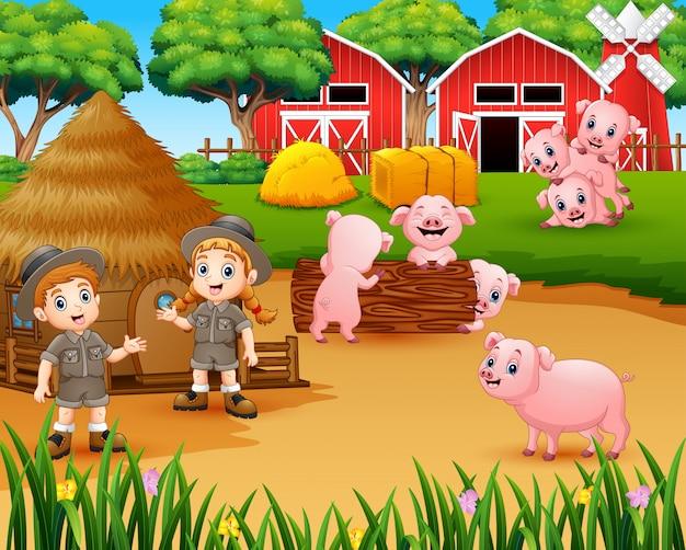 Ragazza e ragazzo dello zookeeper con i maiali nell'aia