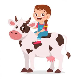 Ragazza felice del bambino sveglio che guida mucca sveglia