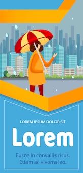 Ragazza in piedi sulla strada con l'ombrello in una giornata piovosa.