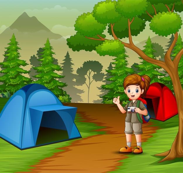 Ragazza in uniforme scout che esplora la foresta