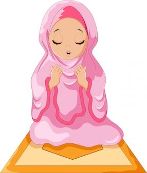 Ragazza musulmana che si siede sul tappeto durante la preghiera