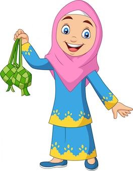Ragazza musulmana sveglia che tiene un ketupat