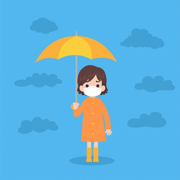 Ragazza sveglia che porta impermeabile arancione che tiene ombrello giallo