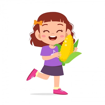 Ragazza sveglia felice del bambino che tiene verdura fresca